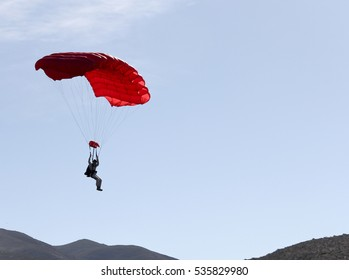 Parachute jumper in a red chute floating back to earth