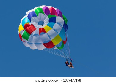 With a parachute for parasailing a couple flies through the air with blue sky in the background.