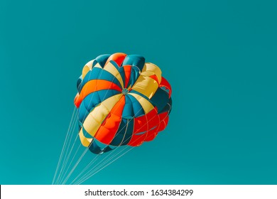 Parachute parasailing of tourists on a sandy beach Sunny weather against the background of clear sea and ocean.The wind blows up the canopy of the parachute against a clear blue sky with clouds