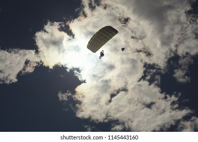 Parachute tandem against the background of clouds and a dazzling sun. Parachute jumping.