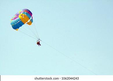 Parachute walk on the sea couple of loving people together on a yellow parachute over the water