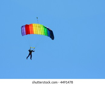Parachuter with colored parachute on sky background 2
