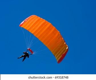 Parachuter descending with a orange parachute against blue sky
