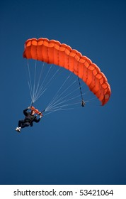 Parachuter descending with a red parachute against blue sky