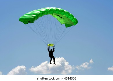 Parachuter  with green parachute on sky background