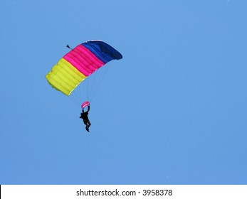 Parachuter on colored parachute on sky background