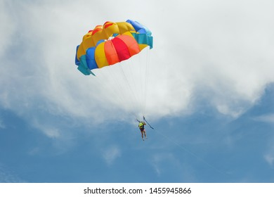 parachuting on vacation by the sea against the blue sky with clouds