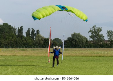 Parachutist with Green Parachute near to the Ground Preparing for Landing.