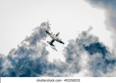 Parachutist, a parachute, out of the door of the aircraft c-130, the background is a little cloudy.