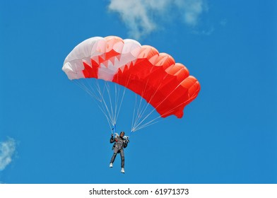 The parachutist under a pink parachute against the blue sky