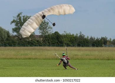 Parachutist with White Parachute near to the Ground Preparing for Landing