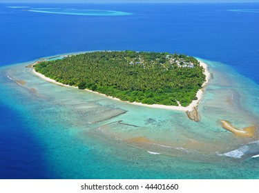 Paradisaic Maldivian island with turquoise beaches, green trees and deep blue sky.