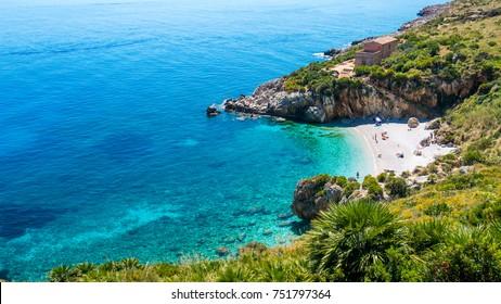 "The paradise beach in Italy: perfect turquoise transparent water, white pebbles surrounded by green. Cove named ""Cala Tonnarella dell'Uzzo"", Natural reserve ""dello Zingaro"", San Vito lo Capo, Sicily."