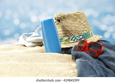 paradise beach and towel of blue and red sunglasses and hat and oil bottle