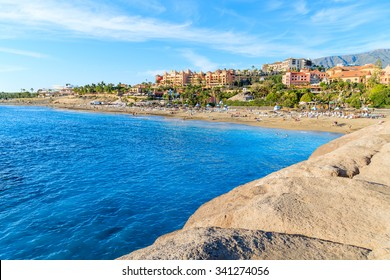 Paradise El Duque beach with azure water and hotels in background in Costa Adeje town, Tenerife, Canary Islands, Spain