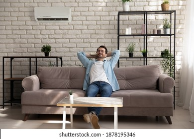 Paradise. Serene young guy with closed eyes reclining on couch at modern designed living room. Carefree millennial male enjoy breathing cool fresh air turn conditioner on using remote control device