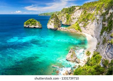 Paradise tropical island with sandy beach, palms trees, reef and rocks, nobody, Nusa Penida, Indonesia