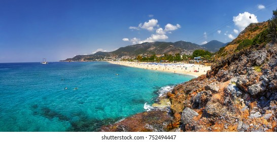 Paradise tropical lagoon with rocky beach in Alanya, Turkey. Sea and mountains landscape in sunny summer day. Alanya beach panoramic view. Tropic bay with rocks on coastline