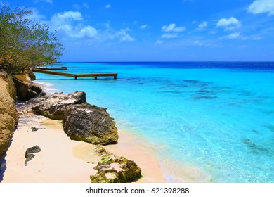 Paradise tropical white fine sandy empty beach with big stones and wooden pier. Calm holiday scene with cyan blue caribbean sea.