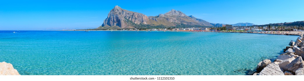 Paradise Tyrrhenian sea bay panorama, San Vito lo Capo beach with clear azure water and extremally white sand, and Monte Monaco in far, Sicily, Italy. People are unrecognizable.