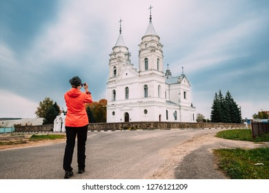 Parafjanava, Dokshitsy District, Vitebsk Region, Belarus. Сhurch Of Name Of Blessed Virgin Mary In Autumn Day. Woman Photographed Orthodox Church. Tourist Taking Photos On Smartphone.
