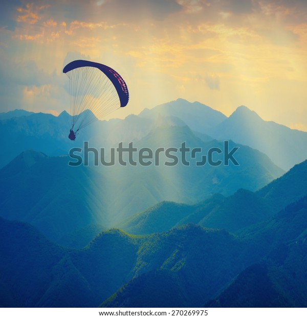 Paraglide silhouette flying over the mountain peaks. Beautiful rays of light in a high mountain valley.