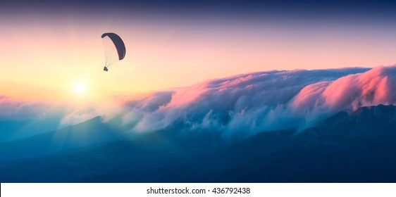 Paraglide silhouette in a light of sunrise above the misty Crimea valley.