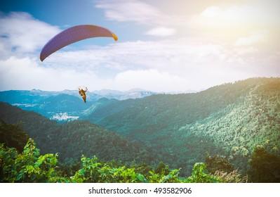 Paraglide silhouette mountain peaks.