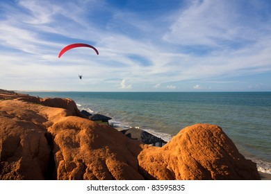 A para-glide soars over a tropical beach backed by red hills