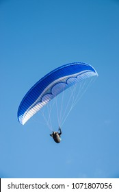 Paraglider in action against a deep blue sky