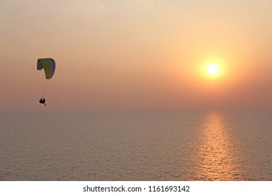 A paraglider against the background of the sea and sunset or dawn. Beautiful seascape. Extreme sport. The paraglider flies over the sea. India, Goa.