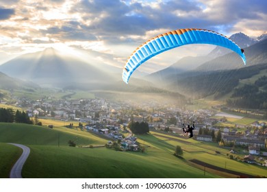 The paraglider in the air over a small mountain town