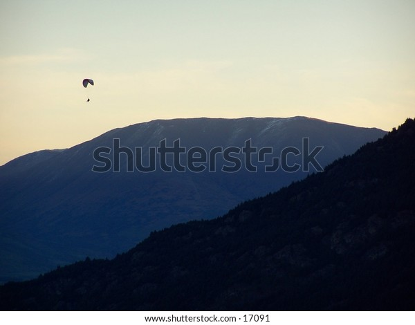 paraglider amongst mountain during sunset