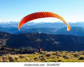 Paraglider in the Bavarian Alpes in front of mountain panorama and blue sky