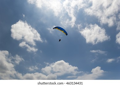 Paraglider in blue cloudy sky. Rear view from the ground. Silhouette of pilot, yellow and blue fabric pattern.