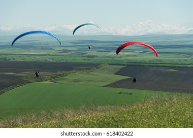 Paraglider flies against the backdrop of fields, land. View from above. Paragliding is not in focus.