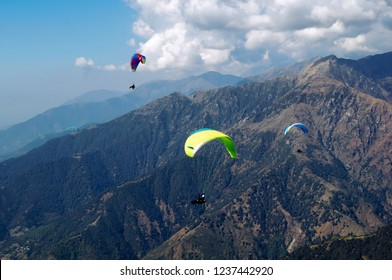 Paraglider flies in the Himalayan mountains. Paragliding in the sky. Mans against the blue sky. Bright athletes fly in the sky. Extreme sport. State in the northern part of India.