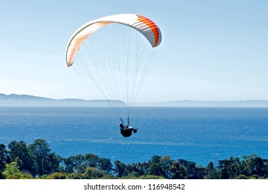 Paraglider flies over the coast of Santa Barbara, California with the Pacific Ocean in the background.