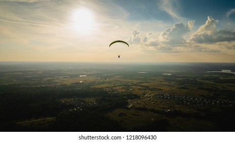 Paraglider flies over the field and forest. The setting sun. Beautiful light. Feeling of freedom. Adrenalin. Extreme Sunset