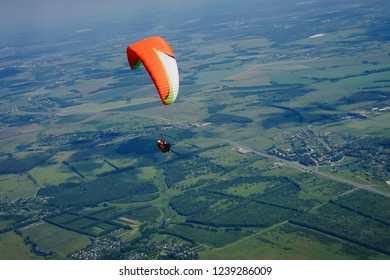Paraglider flies over green fields. High altitude. The athlete turns the thermal current. Rise up. Weather for flights. Top view of the paraglider flying over a green field with a road. Satisfaction.