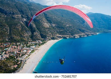 The paraglider flies over the sea in Oludeniz in Turkey. The red wing flies over the blue sea. Extreme sport.
