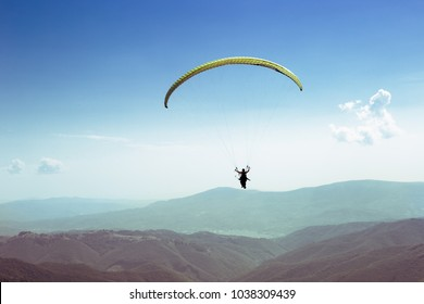 paraglider flies. paraglider over the tops of the mountains in summer sunny day.