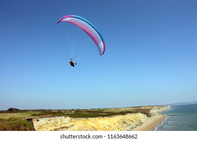 paraglider flies through the air above the sea, on a background of the blue sky. Balance, extreme sports, active lifestyle. English canal, Barton-on-sea, England
