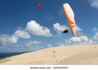 parapente en vol faisant aile sur la dune de Pyla avec ciel bleu et nuage en Gironde