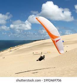 Parapente en vol faisant aile au sol sur la dune de Pyla avec ciel bleu et nuages.