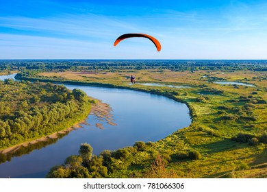 Paraglider flyes over the river in Russia
