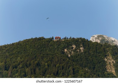 Paraglider flying above a house on the mountain top above Lake Annecy France