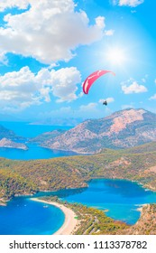 Paraglider flying above Oludeniz beach with rainbow - Fethiye- Turkey.