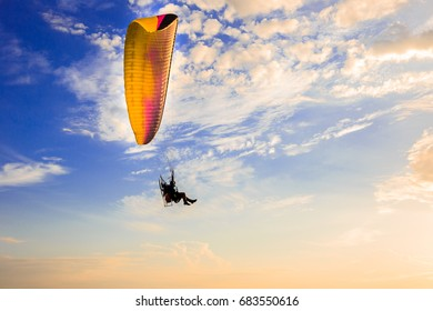 Para-glider flying in the blue sunny sky with clouds, Paragliding