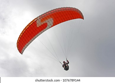 Paraglider flying in a cloudy sky